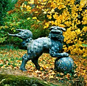 A BRONZE CHINESE LION STANDS IN FRONT OF ACER SACCHARUM. BATSFORD ARBORETUM  GLOUCESTERSHIRE