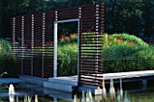 WATER GARDEN WITH ENTRANCEWAY AND METAL WALKWAY  DESIGNED BY ULF NORDFJELL. HEDENS LUSTGARD  SWEDEN