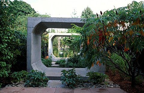 VIEW_DOWN_LONG_THIN_GARDEN_WITH_MASSIVE_CONCRETE_FRAMES__PAVING_AND_RHUS_TYPHINA_STAGS_HORN_SUMACH_D