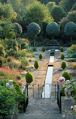 VIEW_FROM_THE_HOUSE_ALONG_THE_RILL_GARDEN_IN_THE_EVENING_WITH_CLIPPED_SHAPES_OF_SORBUS_ARIA_LUTESCEN