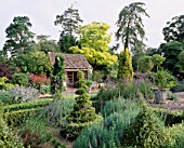 THE SUMMERHOUSE WITH ROBINIA PSEUDOACACIA FRISIA  LARCH SCOTS PINE  LAVENDER  BOX SPIRALS  FASTIGIATE GOLDEN YEW AND CHAMAEOPS HUMILIS. EASTLEACH HOUSE  GLOUCS