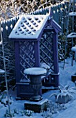 PURPLE COVERED SEAT FLANKED BY METAL URNS AND BACKED BY BLUE DECORATIVE FENCING IN THE NICHOLS GARDEN AT 69  ALBERT ROAD  READING  COVERED WITH SNOW