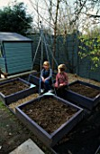 WOODEN SCAFFOLDING BOARDS USED TO MAKE RAISED BEDS FOR THE DECORATIVE CHILDRENS POTAGER PAINTED PALE PURPLE WITH CONNIE AND OLLIE