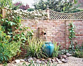GRAVEL COURTYARD WITH WATER FEATURE: BRICK WALL  TRELLIS  WATER SPOUT   TURQUOISE CONTAINER  ROCKS AND CLEMATIS MONTANA