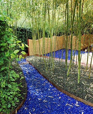 GLASS_GARDEN_BLUE_GLASS_AND_GREEN_MARBLES_ACT_AS_MULCH_BENEATH_BAMBOOS_WITH_ROPE_FENCING_DESIGN_BY_A