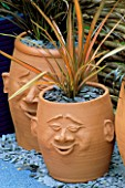 TERRACOTTA POTS WITH FACES PLANTED WITH PHORMIUMS