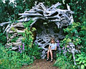 HAZEL SITS IN THE STUMPERY CAVE MADE FROM CANADIAN DRIFTWOOD  DESIGNED BY PHILIP GAME FOR MARNEY HALL
