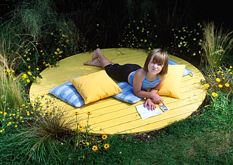 SHANA_HICKS_RELAXES_ON_THE_YELLOW_DECK_CIRCLE_SURROUNDED_BY_RHUS_TYPHINA__BIDENS_AUREA__HELICHRYSUM_