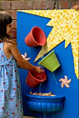 NANCY PLAYS IN THE BUCKET WATER CASCADE: BLUE BOARD WITH YELLOW MOSAIC  COLOURED TERRACOTTA POTS  SHELLS  STARFISH AND RUNNING WATER