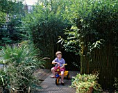 ELLA HATFIELD SITS ON HER BIKE ON WOODEN DECKING BESIDE THE LIVING WILLOW DEN