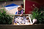 CHILDRENS DECK GARDEN: LUCY FEELING THE SHELLS  FIR CONES AND STONES IN A RAISED WOODEN BED