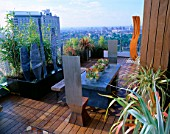 AFRICAN THEMED ROOF TERRACE:IROKO DECKING   HERRINGBONE BRICK DESIGN PANELS.  ZINC-WRAPPED TABLE  STEEL THRONE CHAIRS  CORE-TEN STEEL SHIELD SCULPTURE. DESIGN: S WOODHAMS.
