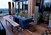 AFRICAN THEMED ROOF TERRACE:IROKO DECKING  HERRINGBONE BRICK DESIGN PANELS.  ZINC-WRAPPED TABLE  STAINLESS STEEL THRONE CHAIRS  CORE-TEN STEEL SHIELD SCULPTURE. DESIGN: S. WOODHAMS