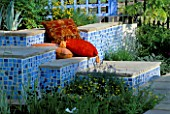 CONCRETE SEATS COVERED WITH MOSAICS AND RED CUSHIONS AT THE HAMPTON COURT FLOWER SHOW 2001. DESIGNER ELIZABETH APEDAILE/DOVE LANDSCAPES
