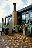 AFRICAN THEMED ROOF TERRACE: IROKO DECKING WITH INSET HERRINGBONE DESIGN PANELS IN COLOURED WOOD. ZINC-WRAPPED TABLE  STAINLESS STEEL THRONE CHAIRS.  DESIGN: S. WOODHAMS