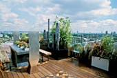 AFRICAN THEMED ROOF TERRACE: VIEW OVER LONDON. WATER FEATURE IN BLACK POWDER-COATED CONTAINER  FIVE LEAD SCULPTURES BY SHAUN BROSNAN.  IROKO DECKING.  DESIGN: S. WOODHAMS