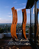 AFRICAN THEMED ROOF TERRACE: THREE CORE-TEN STEEL AFRICAN SHIELDS  FRAMEWORK OF PEBBLES   COPPER UPLIGHTERS  GLASS BALUSTRADE AND IROKO DECKING.  DESIGN: S. WOODHAMS
