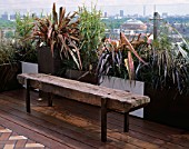AFRICAN THEMED ROOF TERRACE: A PLACE TO SIT: RAILWAY SLEEPER BENCH  GLASS BALUSTRADE   CONTAINERS WITH PHORMIUM TENAX RAINBOW QUEEN & P.PLATTS BLACK. DESIGN: S. WOODHAMS