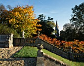 VIEW TOWARDS THE CHURCH FROM THE STEPS AT ENGLEFIELD HOUSE  BERKSHIRE  WITH RHUS TYPHINA AND STONE BALUSTRADE