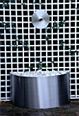 WATER FEATURE: STAINLESS STEEL DISC AND SPOUT POURS INTO A STAINLESS STEEL CONTAINER WITH WHITE PEBBLES. WHITE TRELLIS BEHIND. DESIGN: CLARE MATTHEWS. TRELLIS BY ASTOR TRELLISWORK