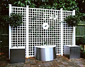 WATER FEATURE: STAINLESS STEEL DISC AND SPOUT POURS INTO CONTAINER WITH WHITE PEBBLES. WHITE TRELLIS BEHIND. DESIGN: CLARE MATTHEWS. TRELLIS BY ASTOR TRELLISWORK