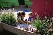 CHILDRENS DECK GARDEN: LUCY  AND CLARE FEELING THE SHELLS  FIR CONES AND STONES IN A RAISED WOODEN BED: DESIGNER: CLARE MATTHEWS