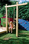 CHILDRENS DECK GARDEN: LUCY  SITS ON A WOODEN SWING: DESIGNER: CLARE MATTHEWS