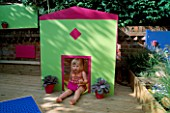 CHILDRENS DECK GARDEN: LUCY PLAYS OUTSIDE THE FOLDAWAY WENDY HOUSE ON THE DECK WITH