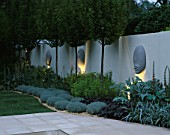 THE SANCTUARY GARDEN  CHELSEA 2002  LIT UP AT NIGHT. DESIGNER: STEPHEN WOODHAMS:WALL WITH  5 FACE SCULPTURE BY STEPHEN COX