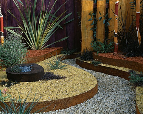 KELLYS_CREEK_GARDEN__CHELSEA_2002_LINES_OF_COLOURED_GRAVELS_ON_DIFFERENT_LEVELS__PHORMIUM_TENAX_VARI