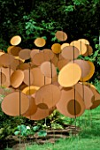 DISCS OF COPPER COLOURED NYLON BALLOON FABRIC BY PAUL LANGH IN THE HARBOUR UNDER SAIL GARDEN AT THE WESTONBIRT FESTIVAL OF GARDENS 2002