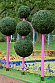 WESTONBIRT FESTIVAL OF GARDENS  2002: THE FANTASY GARDEN BY CANDACE BAHOUTH: ARTIFICIAL TOPIARY BALLS ON PINK WOODEN POLES