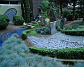 HELTER SKELTER   GARDEN CREATED BY TONY HEYWOOD OF CONCEPTUAL GARDENS  LONDON: BOX HEDGING  FESTUCA GLAUCA  ROCKS  SLATE  A CURVED MIRROR OF MARINE STEEL & TWISTED LEAD