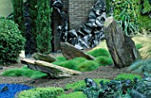 HELTER SKELTER   GARDEN CREATED BY TONY HEYWOOD OF CONCEPTUAL GARDENS  LONDON: ROCKS  GRASSES  TWISTED LEAD AND YEW TOPIARY