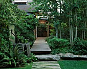 VIEW ALONG FRONT WOODEN PATH WITH LAWN  STONE WATER FEATURE WITH COPPER PIPE  ROCK  DECKING AND ASPENS. DESIGNER BOB SWAIN  SEATTLE  USA
