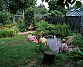 CHILDREN PLAYING BESIDE THEWILDLIFE POND IN ROSEMARY PEARSONS GARDEN  READING  WITH THE POTAGER IN THE BACKGROUND