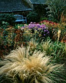 PETTIFERS GARDEN  OXFORDSHIRE: AUTUMN BORDER WITH BLUE BENCH BY NICHOLAS HODGES  SEDUM AUTUMN JOY   ASTER FRIKARTII  ACHILLEA WALTHER FUNCKE  KNIPHOFIA AND STIPA TENUISSIMA