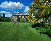 THE HOUSE AND LAWN WITH LABURNUM ON THE RIGHT. DESIGNER: ANGEL COLLINS