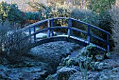 FROSTED BLUE WOODEN BRIDGE OVER A SMALL STREAM  AT THE LANCE HATTATT DESIGN GARDEN AT ARROW COTTAGE  HEREFORDSHIRE