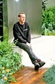 GARDEN DESIGNER STEPHEN WOODHAMS SITS ON THE WATER FEATURE. SANCTUARY GARDEN SPONSORED BY MERRILL LYNCH AT THE CHELSEA FLOWER SHOW 2002: DESIGNED BY STEPHEN WOODHAMS: