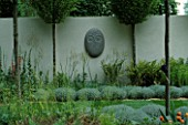 SANCTUARY GARDEN SPONSORED BY MERRILL LYNCH AT THE CHELSEA FLOWER SHOW 2002: DESIGNED BY STEPHEN WOODHAMS: ONE OF THE FIVE FACE SCULPTURES BY STEPHEN COX BESIDE CLIPPED SANTOLINA