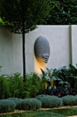SANCTUARY GARDEN SPONSORED BY MERRILL LYNCH AT THE CHELSEA FLOWER SHOW 2002: DESIGNED BY STEPHEN WOODHAMS: ONE OF THE FIVE FACE SCULPTURES BY STEPHEN COX WITH LIGHTING