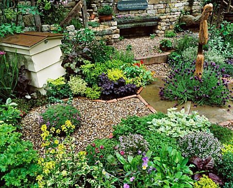 VIEW_ACROSS_HERB_SOCIETYS_GARDEN__CHELSEA_2003_CHIVES_SURROUND_CENTRAL_WOODEN_FEATURE_BY_JON_EDGAR_W