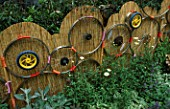 CHELSEA FLOWER SHOW 2003. DESIGNER: POZ MARTIN AND DEENA KESTENBAUM: FENCE MADE FROM RE-CYCLED BICYCLE WHEELS