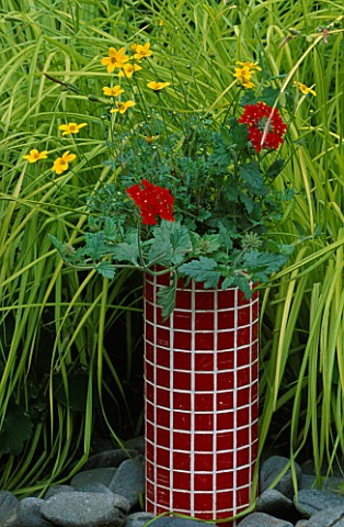 DESIGNER_CLARE_MATTHEWS_RED_MOSAIC_TUBE_CONTAINER_PLANTED_WITH_BIDENS_YELLOW_BREEZE_AND_VERBENA_SUNM