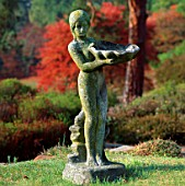 STATUE OF GIRL HOLDING SHELL BIRDBATH  WITH AUTUMN COLOURS IN B/G.  PYRFORD COURT  SURREY.