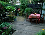 SMALL TOWN GARDEN WITH DECKING  PAVING  TABLE AND CHAIRS  TRACHYCARPUS FORTUNEI AND HAMMOCK. DESIGNER: SARAH LAYTON