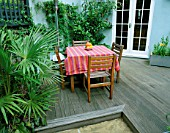 SMALL TOWN GARDEN WITH DECKING  PAVING  TABLE AND CHAIRS AND TRACHYCARPUS FORTUNEI. DESIGNER: SARAH LAYTON