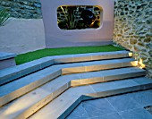 SMALL COURTYARD WITH STEPS AND RENDERED CONCRETE APERTURE WITH SCULPTURE  LIT UP AT NIGHT. DESIGNER: AMIR SCHLEZINGER/MY LANDSCAPES