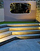 STEPS AND RENDERED CONCRETE APERTURE WITH JELLY PALM (BUTIA CAPITATA) AND SCULPTURE LIT UP AT NIGHT IN SMALL COURTYARD. DESIGNER: AMIR SCHLEZINGER/MY LANDSCAPES